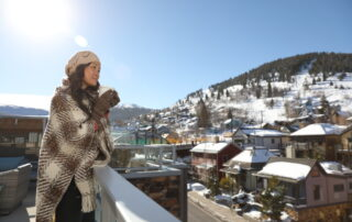 Woman with Coffee on Balcony Overlooking Downtown Park City