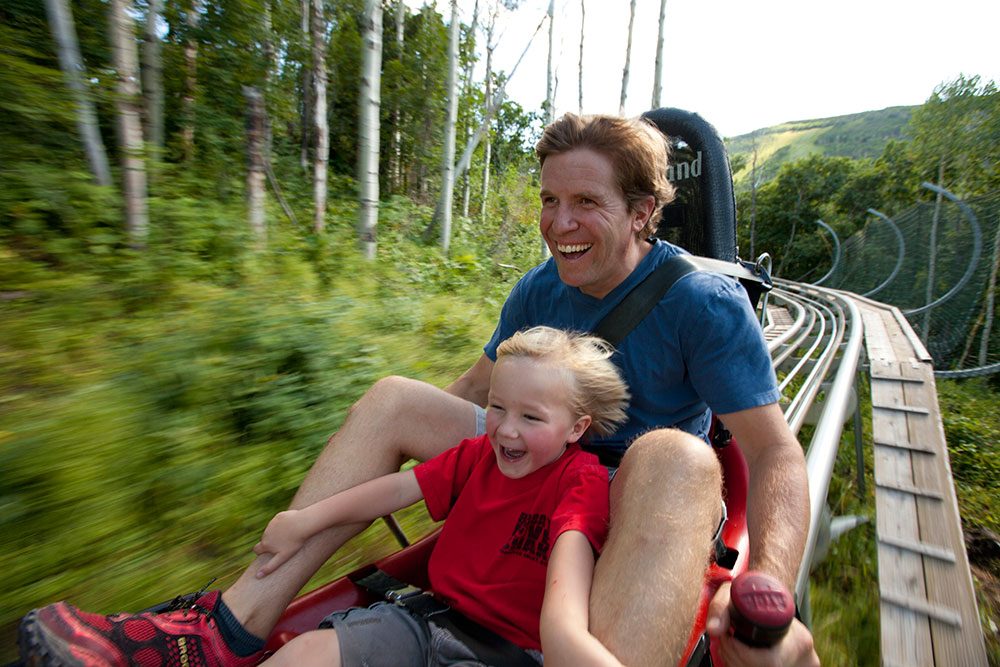 Father and Child Riding Alpine Slide in Summer