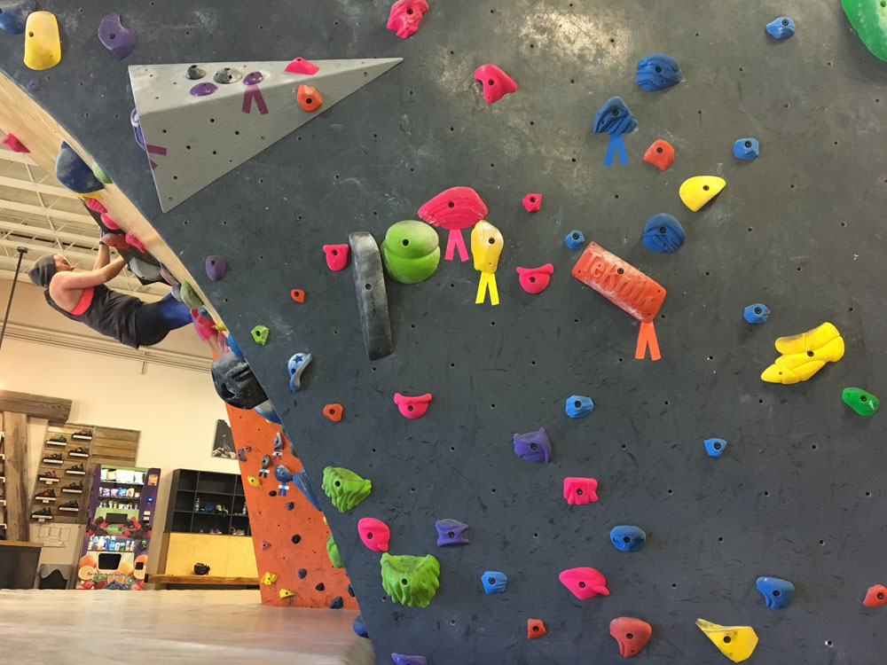 Rock Climber on a Boldering Wall at a Rock Gym