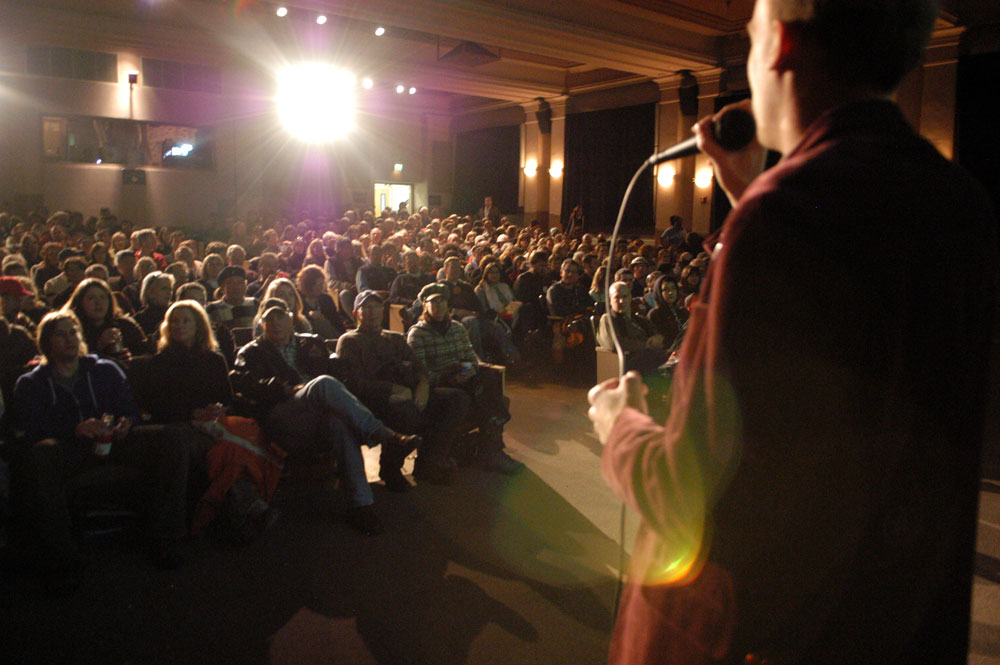 Speaker on Stage in front of a Crowd of Seated People