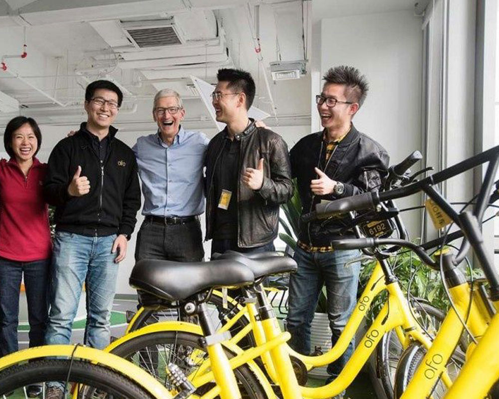 Group in front of yellow ride share bikes
