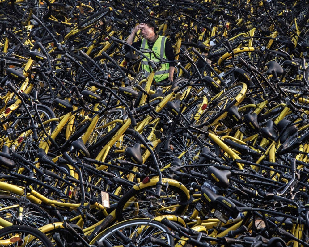 Man overwhelmed by stacks of discarded bikes