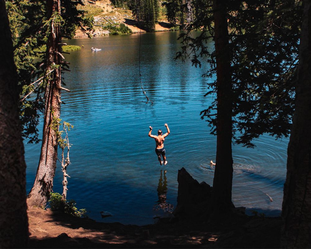 Boy uses rope swing at Bloods Lake