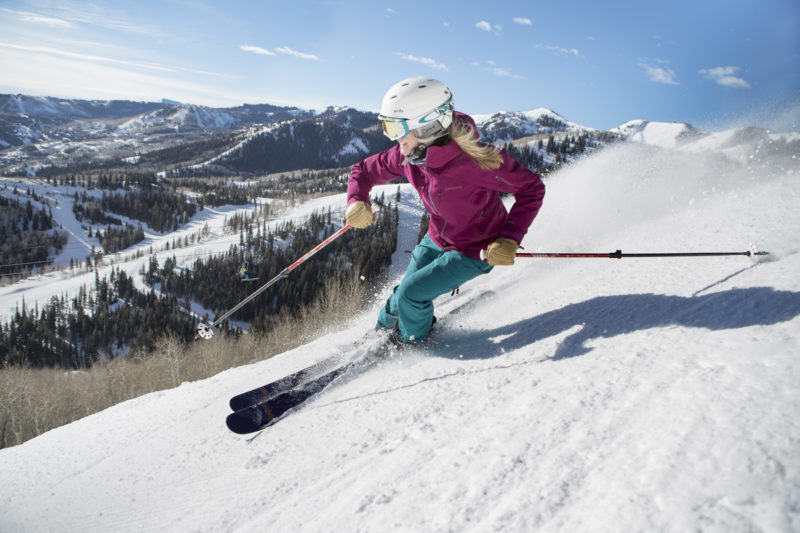 woman skiing on a bluebird day in park city utah