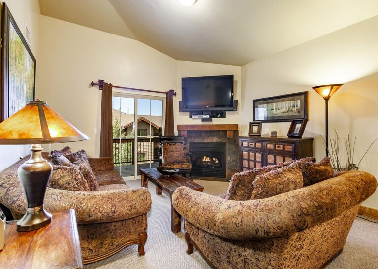 Spacious living rooms in 3-bedroom Bear Hollow Village condos include TVs and fireplaces