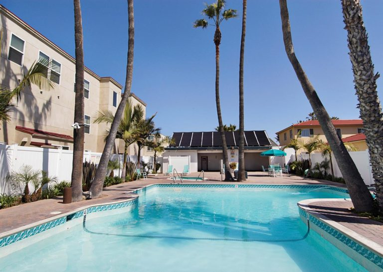 Outdoor Pool with Towering Palm Trees at Capri by the Sea in San Diego, California