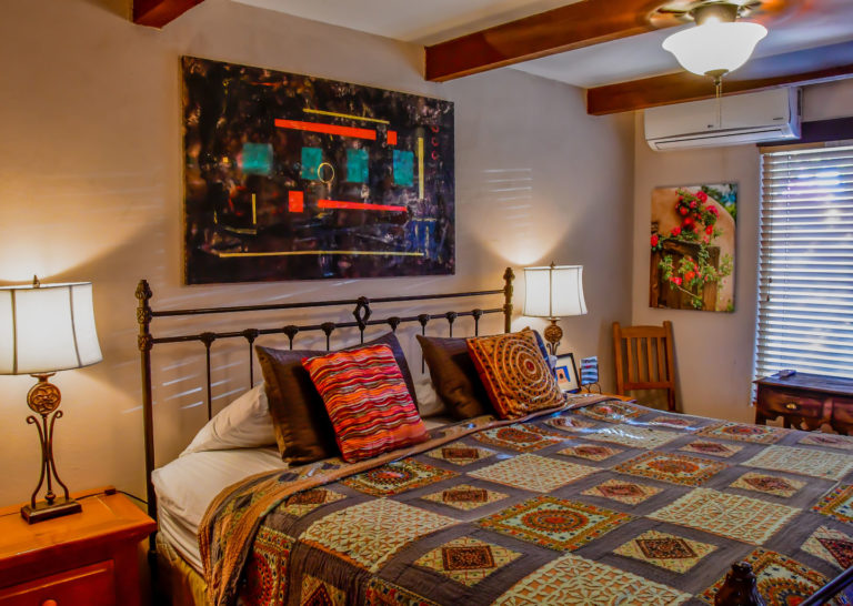 Bedroom with Abstract Art and Exposed Beams at Fort Marcy Hotel Suites in Santa Fe, New Mexico