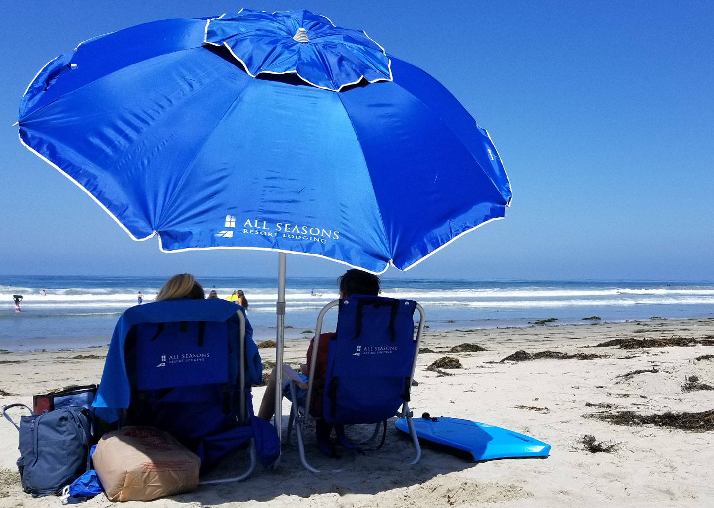 Two Beach Bathers Resting Under a Blue All Seasons Resort Lodging Umbrella on a Sunny Day