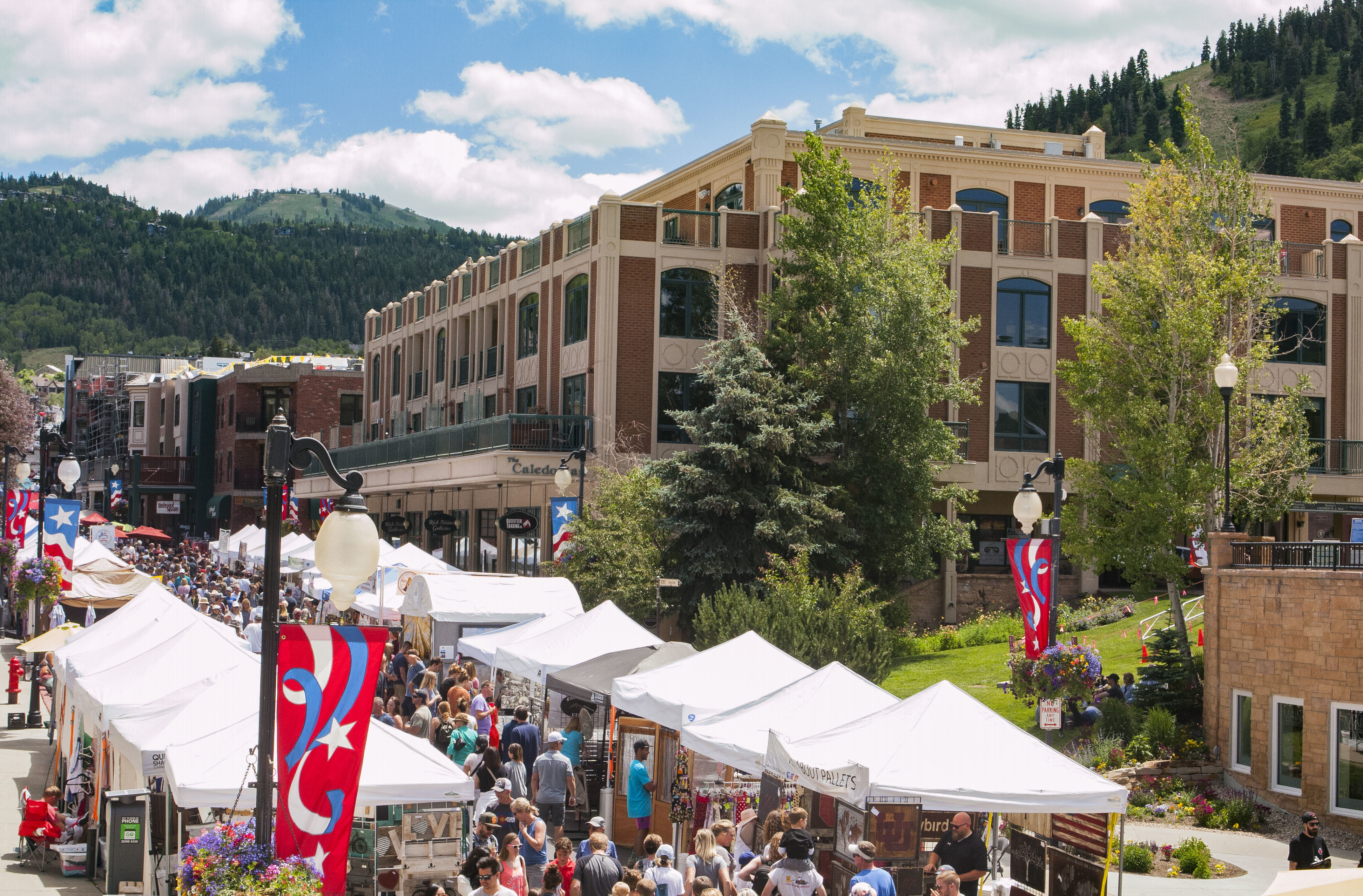 Festival in Summer on Main Street Park City, Deer Valley Rises in the Background and The Caledonian Hotel is Featured in the Midground