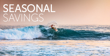 Seasonal Savings Promo Image with Man Surfing a Wave at Sunset