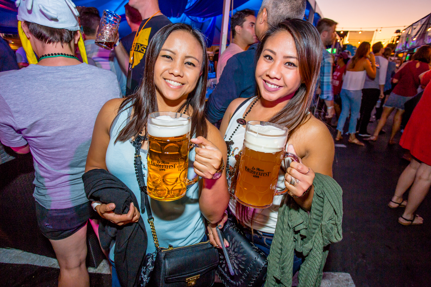 Two Ladies Cheers with Full Steins of Beer