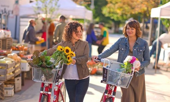Two Women Walking Their Bikes with Flowers in the Baskets