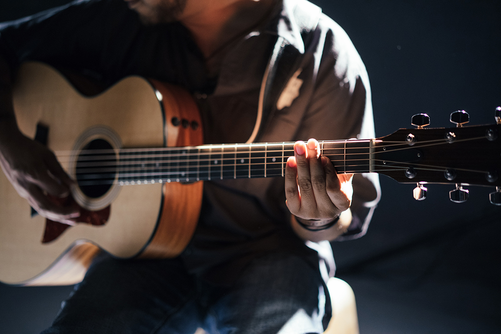 Man Playing Guitar in the Spotlight