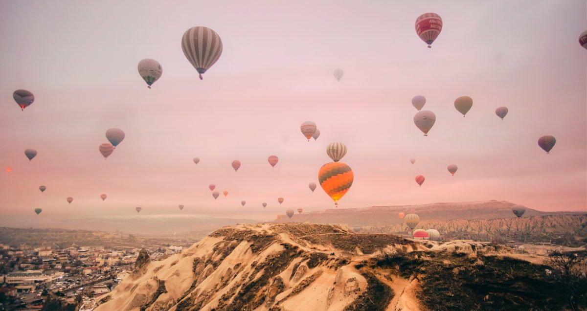 Many Hot Air Balloons Rising Against a Pink Sky