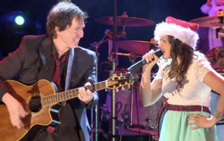 Man playing guitar with woman dressed in Santa hat