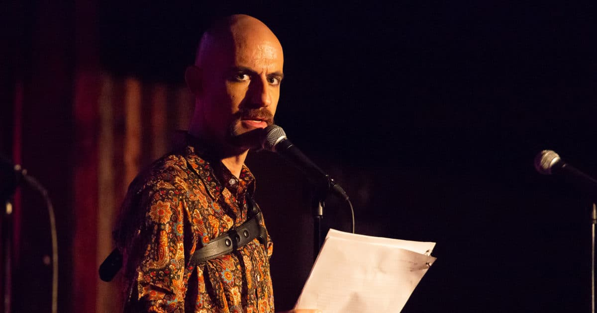 Bald Man Reciting From a Paper on Stage