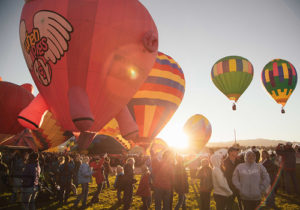 Hot Air Balloons Taking Flight at Dawn with a Crowd of Spectators Looking on