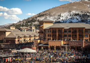 Aerial View of Sundial Lodge in Early Spring with Crowd of People at the Mountain Base Area of Canyons Village
