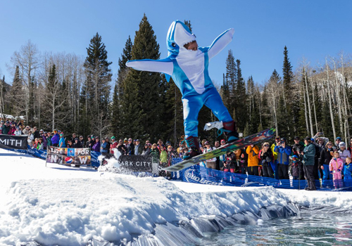 Snowboarder in Shark Suit Jumping Over Icy Pond at Park City Mountain Resort