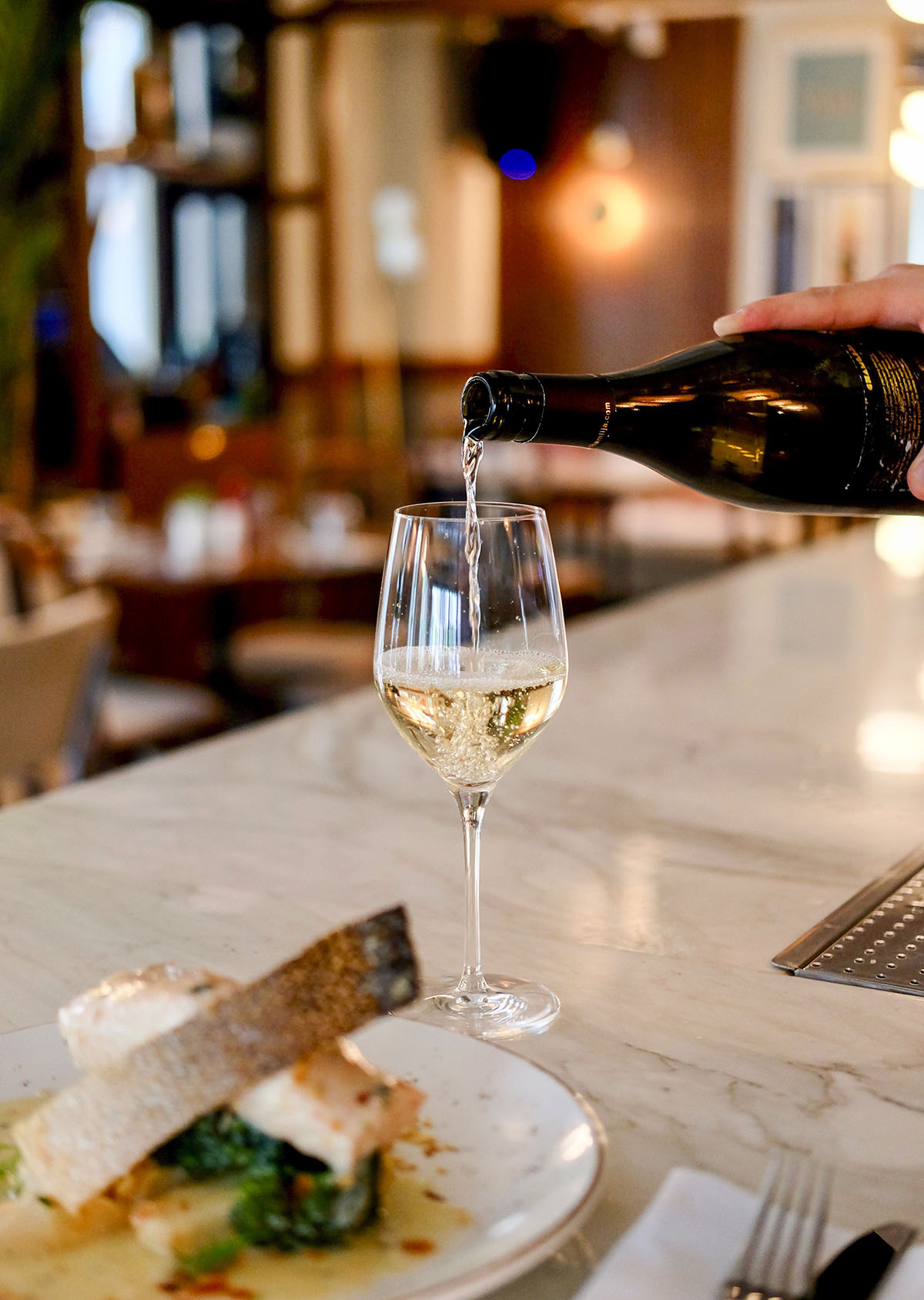 Glass of White Wine on a White Marble Bar