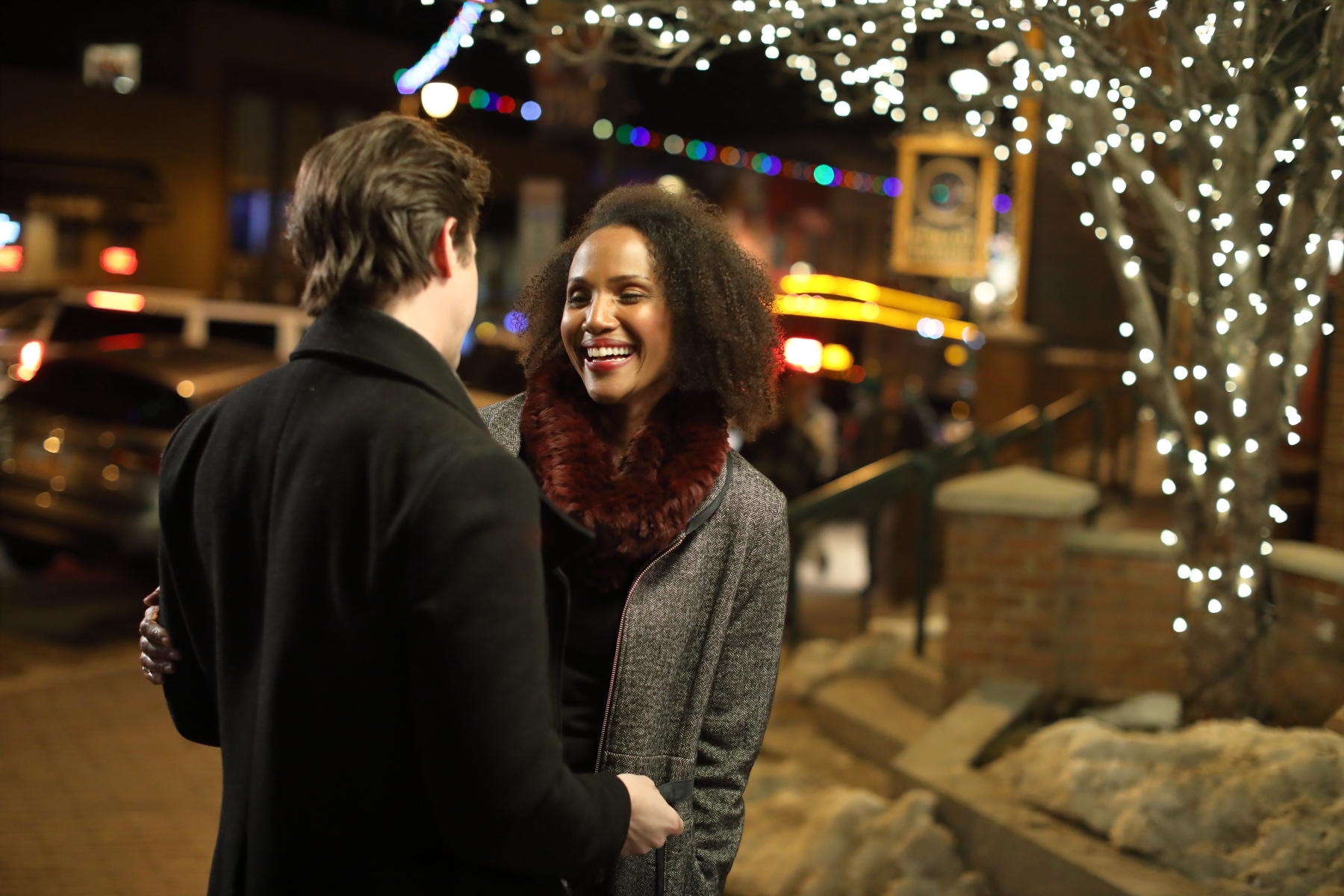 Couple embracing under Christmas lights on Main Street Park City