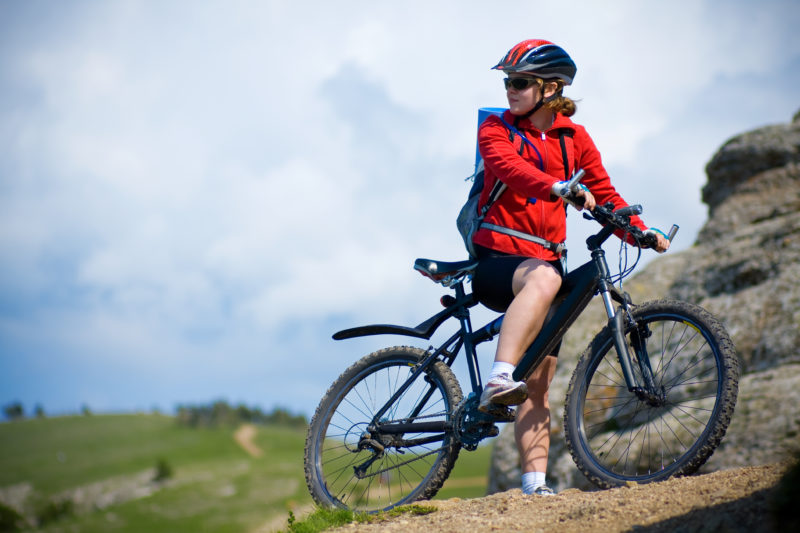 woman mountain biking in the mountains in spring