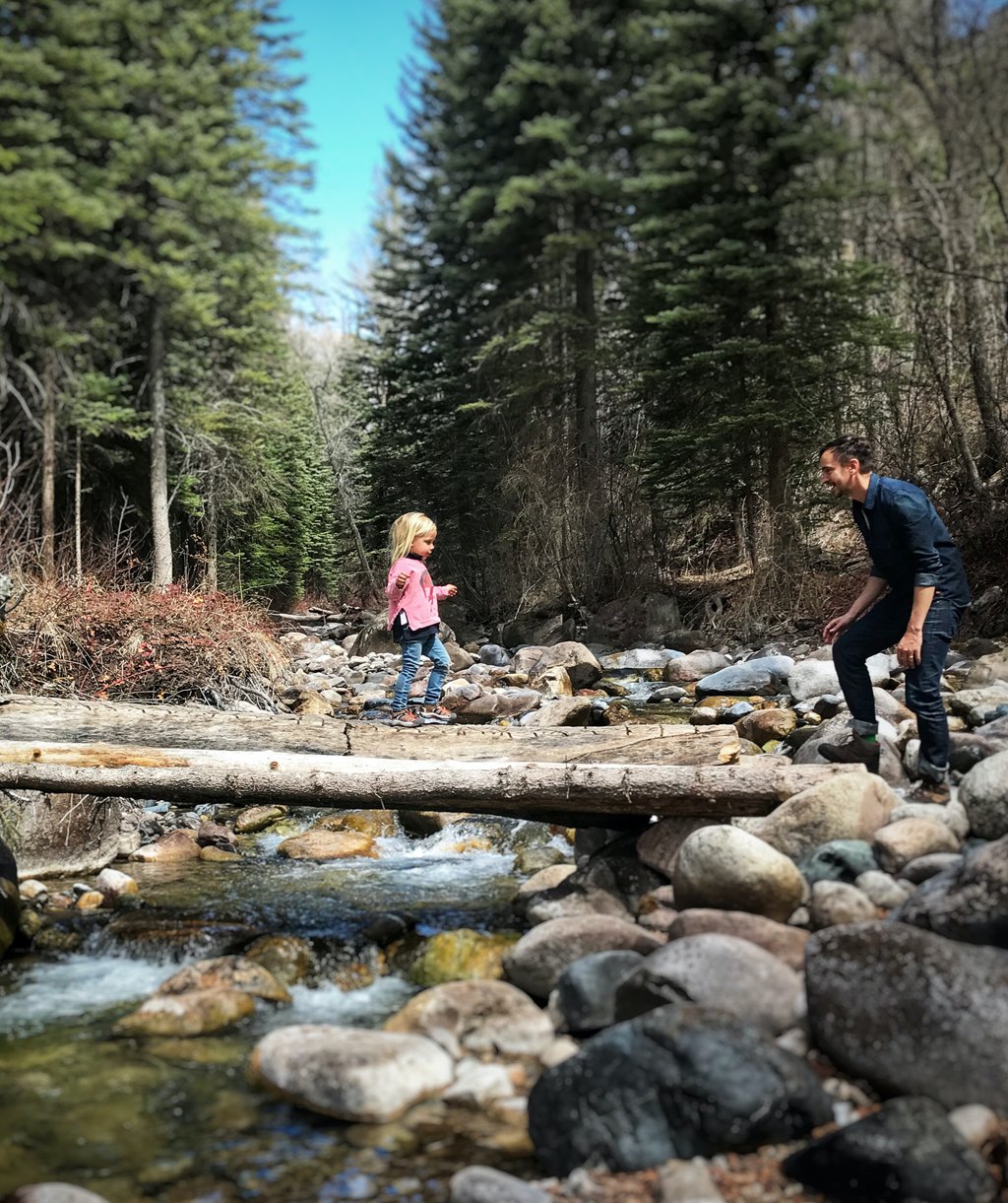 Daughter Walking Across a Fallen Tree to Her Father's Outstretched Arms on a Park City Hike