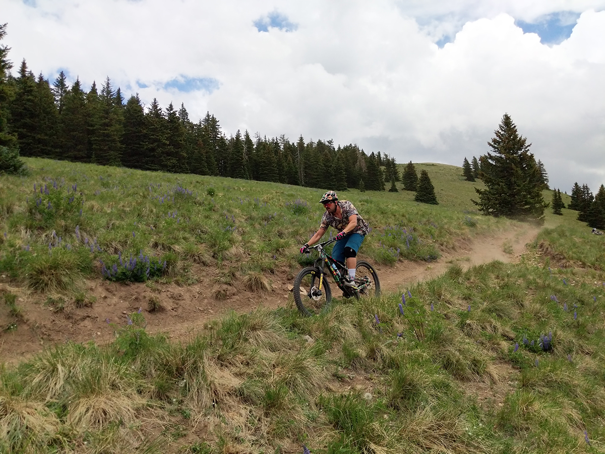 man mountain biking on dirt trail in the mountains