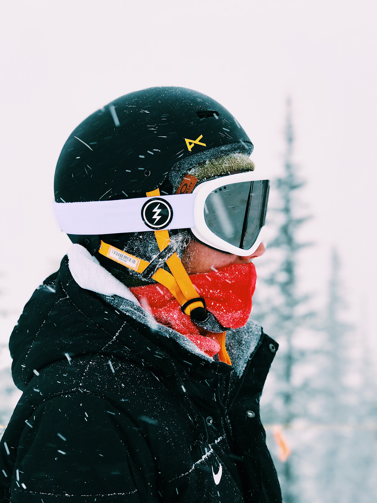 Profile view of a skier in a helmet and mask on snowy day in Park City
