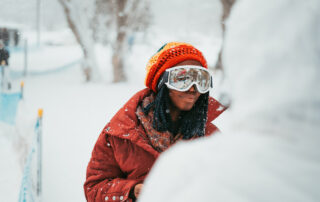 Woman Standing in Fresh Snow Wearing Cozy Red Jacket in Park City