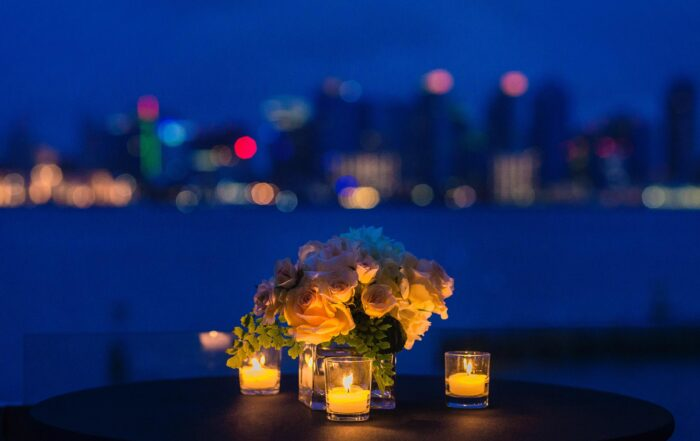 Romantic candlelit dinner with roses overlooking San Diego bay and skyline at dusk
