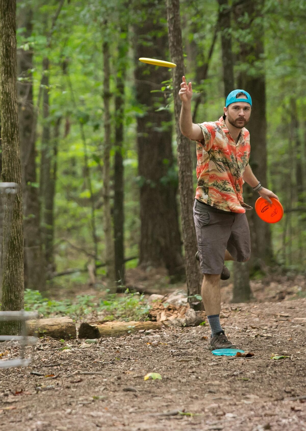 man throwing frisbee towards camera in the forrest