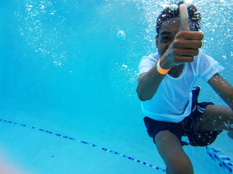 A Happy Boy Giving a Thumbs Up Underwater in the Pool in Park City