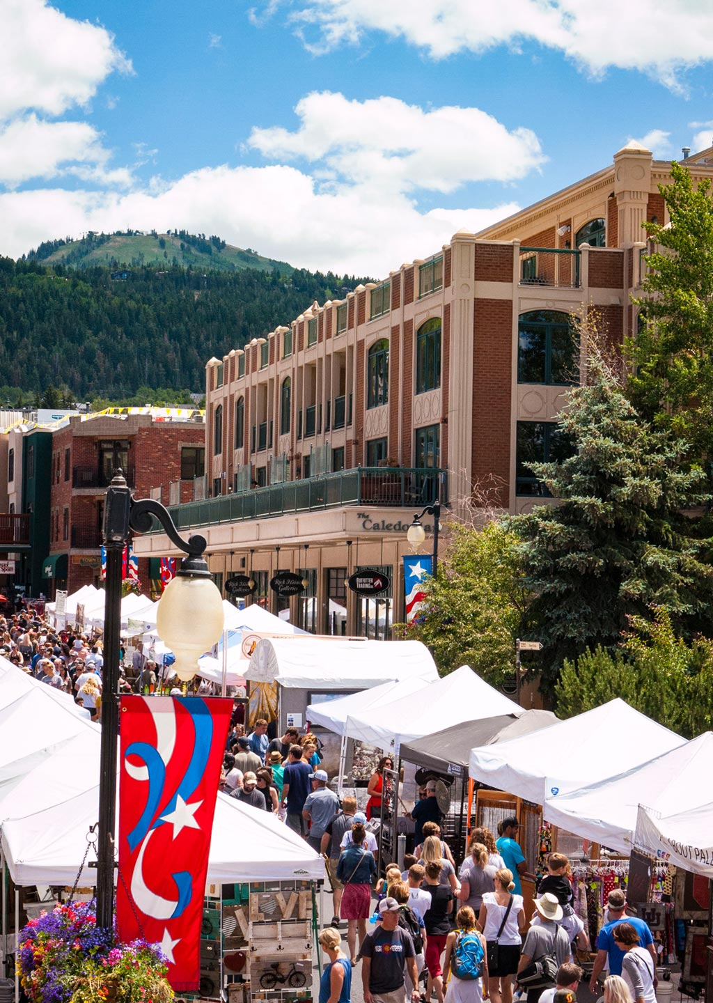 Park Silly Sunday festival on Main Street Park City during summer time. The Caledonian Hotel in the mid-ground, Deer Valley rises in the background