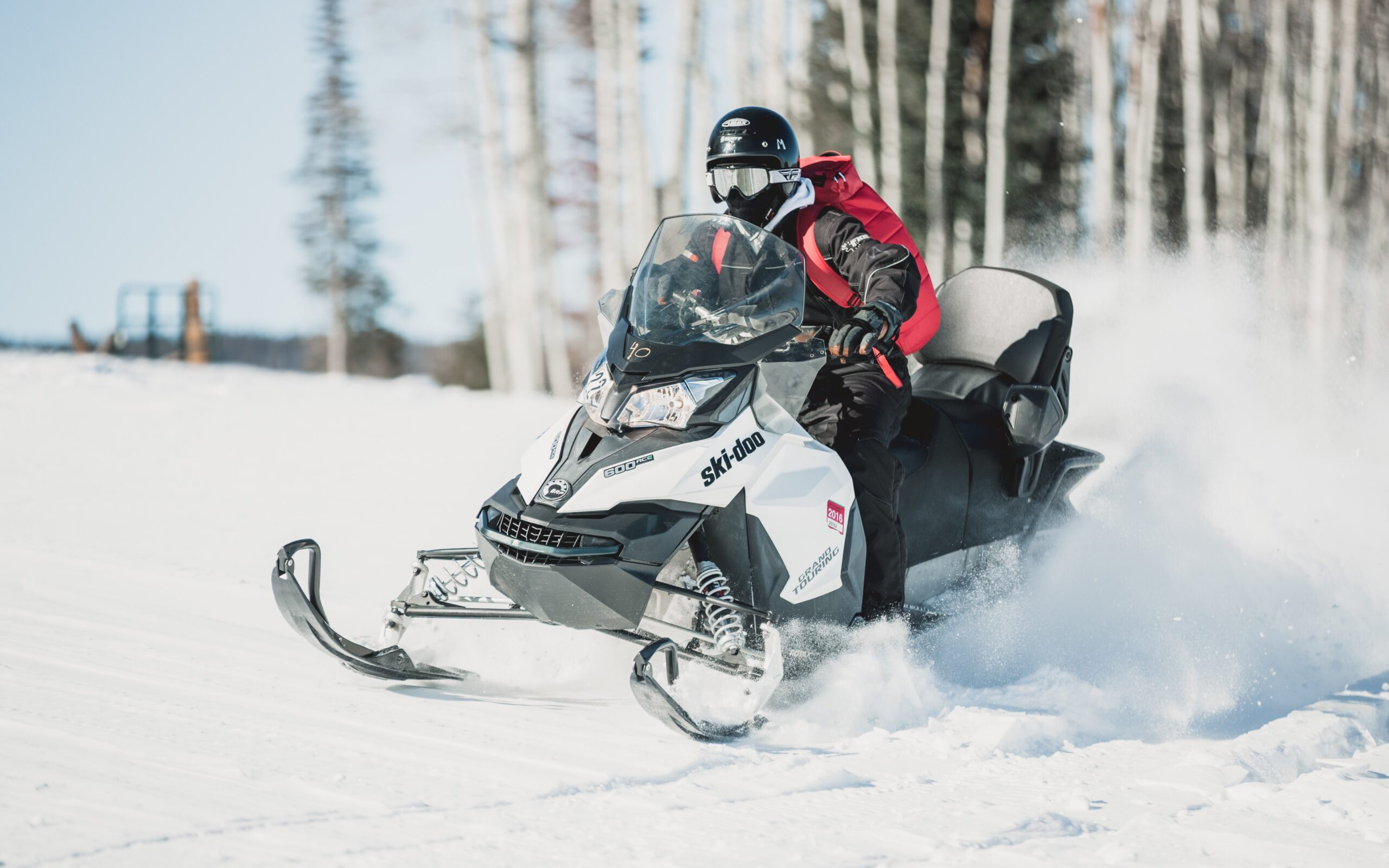 Snowmobiler Riding Across Snow Covered Field