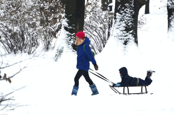 Mother Pulling Child on Sled in the Snow