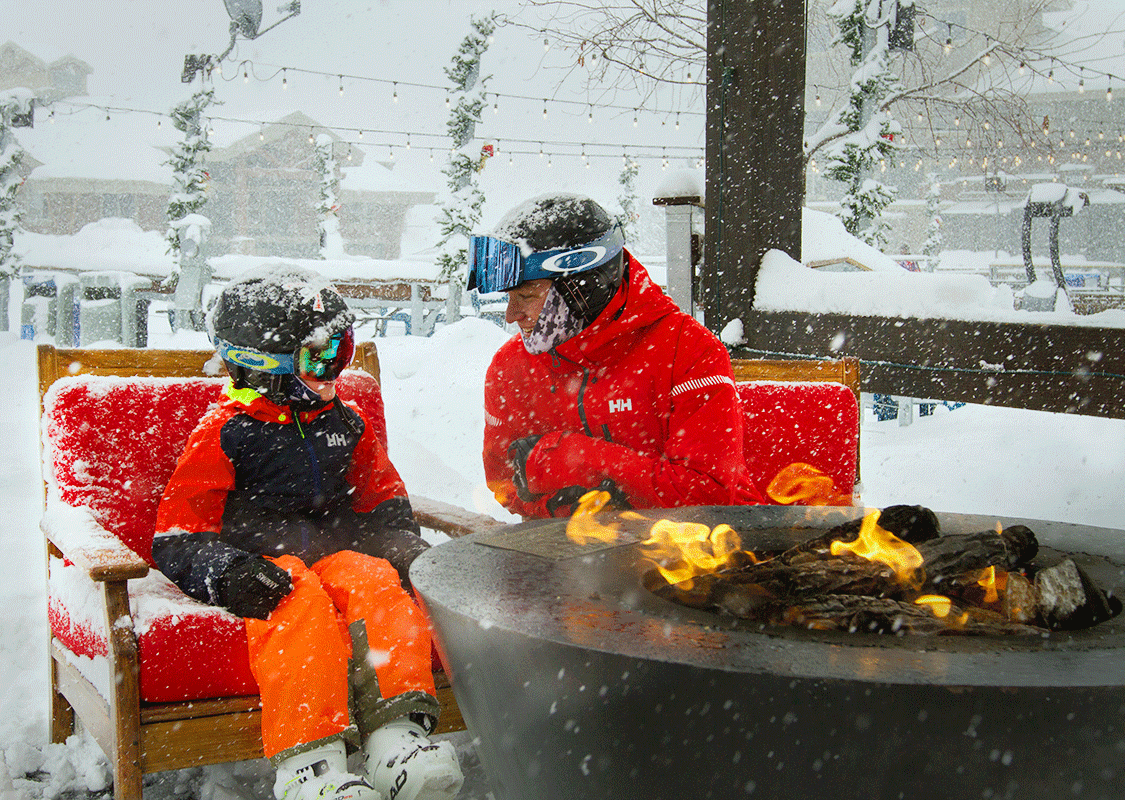 Father and Son Sitting by a Fire in a Snowstorm in Park City